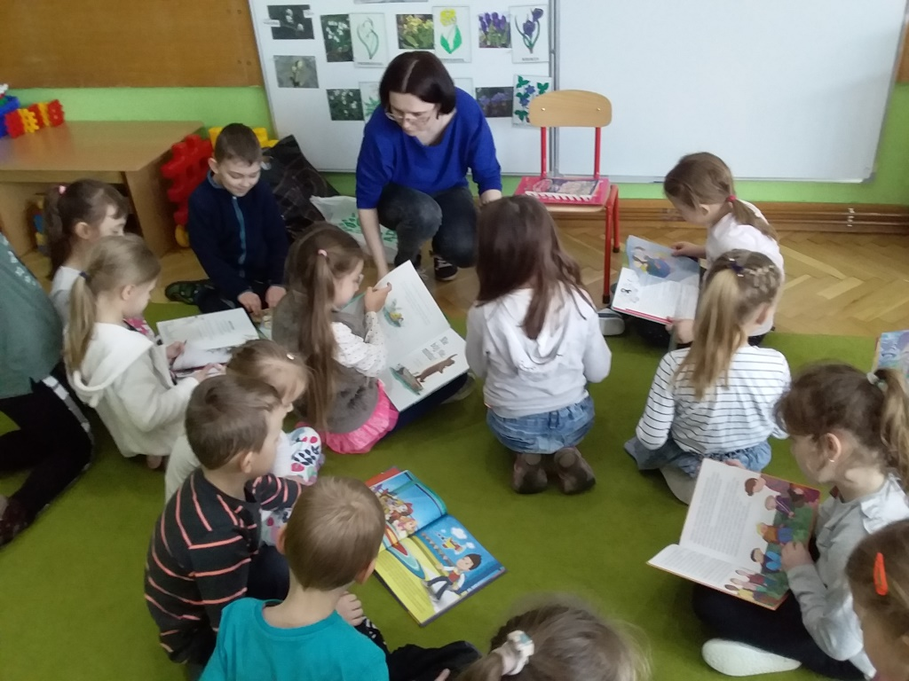 Przedszkolaki na odłodze oglądają książeczki.